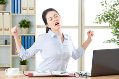Asian businesswoman fell tired and stretching - stock photo