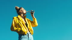 Young hipster woman in yellow jacket drinking water from a bottle Stock Footage