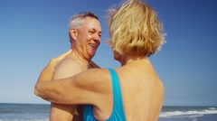 Caucasian seniors in swimwear dancing on the beach by the ocean Stock Footage