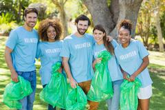 Portrait of volunteer group posing while collecting rubbish in park Stock Photos