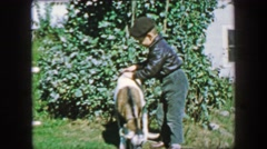 1957: Boy petting tied up farm goat on green grass acred country villa. Stock Footage