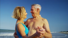 Happy mature Caucasian couple in swimsuits dancing on the beach vacation Stock Footage