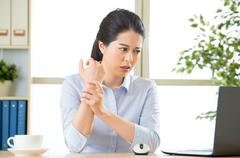 Young asian business woman with pain in wrist Stock Photos