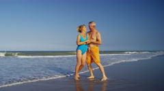 Happy retired Caucasian couple in swimsuits dancing on the beach Stock Footage