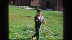 1957: Boy proudly hand feeding sheep bottle of milk at country farm. Stock Footage