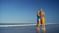 Happy Caucasian seniors in swimwear dancing on the beach Stock Footage