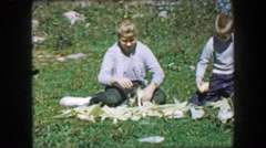 1957: Sibling feeding chickens freshly picked ears of corn from the farm. Stock Footage