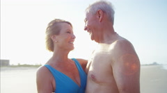 Smiling mature Caucasian couple in swimwear dancing together on the beach Stock Footage