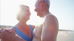 Romantic senior Caucasian couple in swimwear dancing on the beach Stock Footage