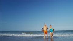 Happy Caucasian seniors in swimwear running with bodyboards on the beach Stock Footage