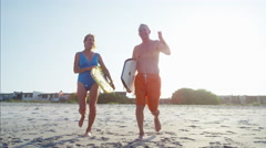 Senior Caucasian couple in swimwear running with bodyboards on the beach Stock Footage