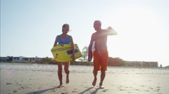 Mature Caucasian couple in swimsuits running with body boards on the beach Stock Footage