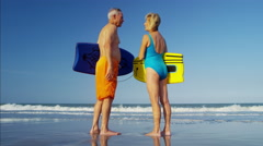 Senior Caucasian couple in swimwear with body boards on beach vacation Stock Footage
