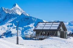 Mountain Chalet amongst snow capped peaks. High Resolution Photo. Stock Photos