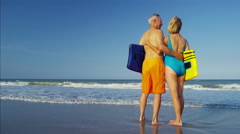 Loving Caucasian seniors in swimwear relaxing with body board on the beach Stock Footage
