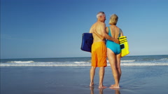 Happy retired Caucasian couple in swimwear with bodyboards enjoying the beach Stock Footage