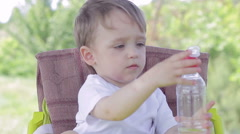 Child boy sitting at a table on the nature drinks water from a bottle Stock Footage