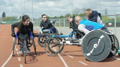 4K Portrait of smiling disabled athlete at race track with team mates chatting Stock Footage