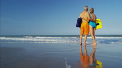 Mature Caucasian couple in swimwear with bodyboards sharing a kiss on the beach Stock Footage