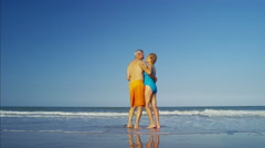 Loving senior Caucasian couple in swimwear sharing kiss on the beach Stock Footage