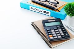 Accounting work background with calculator on notebook and space Stock Photos