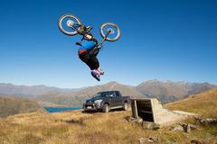 Backflip on Mountainbike above beautiful lake. High Resolution photo. - stock photo