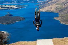 Mountain biker does backflip above lake. High Resolution Photo. - stock photo