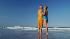 Loving mature Caucasian couple in swimsuits sharing kiss on the beach Stock Footage