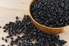 Black beans on wood background Stock Photos