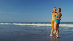 Happy mature Caucasian couple in swimsuits dancing on the beach Stock Footage