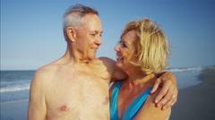 Loving Caucasian seniors in swimwear on beach holiday Stock Footage