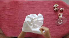 Female hands artistically fold napkin and put it into a glass. Table decoration. Stock Footage