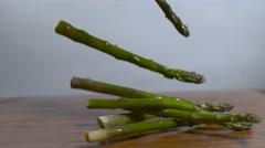 Asparagus falling onto a cutting board in slow motion - Shot on phantom 4k Flex - stock footage