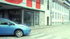 Nissan Leaf electric vehicle is moving between buildings in Stavanger - stock footage