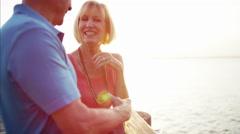 Caucasian seniors on the vacation resort at sunset Stock Footage