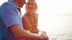 Loving Caucasian seniors on the pier at sunset Stock Footage