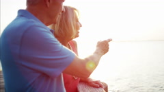 Mature Caucasian couple in colorful clothing on the holiday resort at sunrise Stock Footage