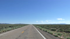POV-Weathered 2 lane road sagebrush flat vanishing in distance Stock Footage