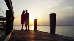 Silhouette of Caucasian seniors on the wharf at sunset Stock Footage