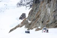 Small red helicoper on alpes mountains Stock Photos