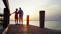 Silhouette of retired Caucasian couple enjoying sunrise on the pier Stock Footage