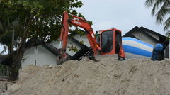 Dam construction with Backhoe along the beach to reduce the waves Stock Footage