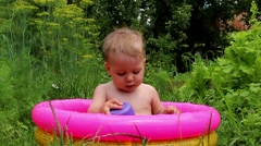 Boy in paddling pool fun Stock Footage