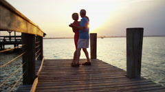 Silhouette of romantic mature Caucasian couple dancing on the wharf at sunrise Stock Footage