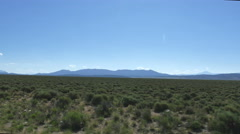 POV-side window flat sagebrush plain distant mountains clear sky Stock Footage