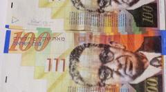 Stack of Israeli money bills of 100 shekel - Tilt down Stock Footage