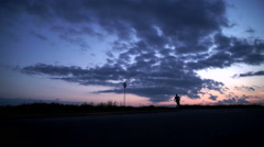 Silhouette of a man running on the road at sunset - stock footage