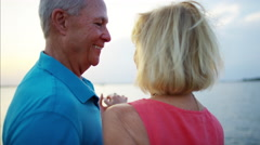 Romantic senior Caucasian couple dancing on the pier at sunset Stock Footage