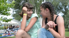 two girls teenagers whisper in the ear of a secret - a picnic in the park - stock footage
