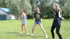 Three girls dancing fun in the summer park on the green grass - stock footage